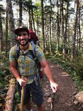 Diego smiles while hiking on a wooded path with a large backpack and two walking sticks.